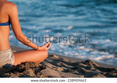 Girl doing meditation on the beach - stock photo