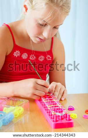 girl doing rubber band bracelet with a loom - stock photo
