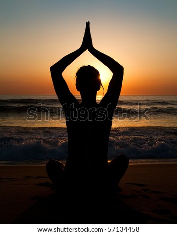 Girl doing yoga at the beach - stock photo