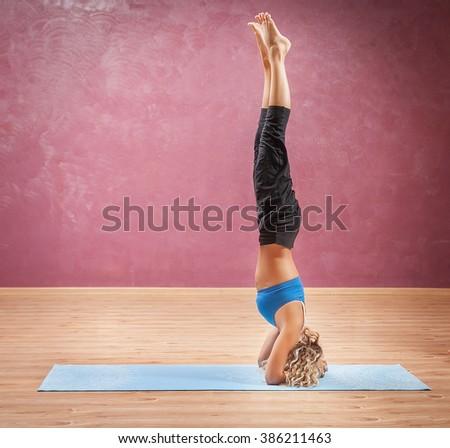 girl doing yoga standing on head. - stock photo