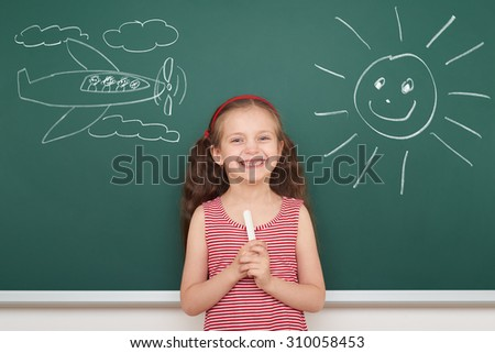 girl draw sun and plane on school board - stock photo