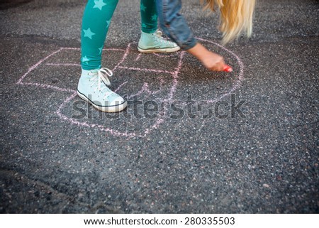 Girl drawing a hopscotch on asphalt with street chalk - stock photo