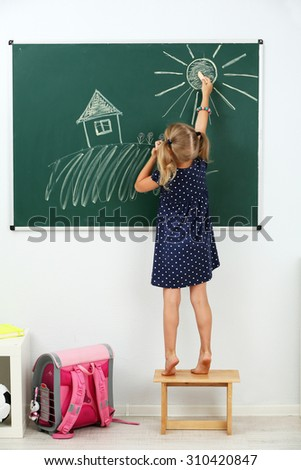 Girl drawing on blackboard at school - stock photo