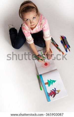 girl draws a picture. Little girl drawing - closeup shot. Portrait of lovely girl holding a pencil? drawing in copybook and looking at camera. - stock photo