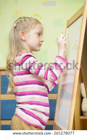 Girl draws on an easel  in the nursery  - stock photo
