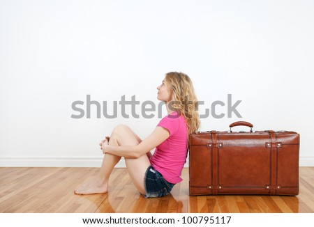 Girl dreaming of vacation, sitting next to a vintage leather suitcase. - stock photo