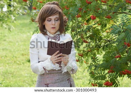 Girl dressed in retro style reads interesting book. Her mouth is slightly open                                - stock photo