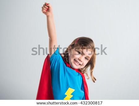 Girl dressed like superhero making fly gesture over grey background - stock photo