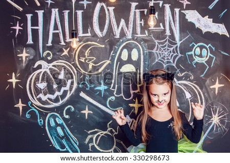 Girl dressed up in Halloween costumes. Posing on the background of the inscription Halloween. - stock photo