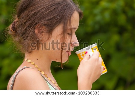 Girl drinking a cup of tea in the park, close-up portrait - stock photo