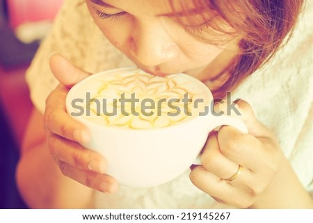 Girl drinking coffee latte vintage color tone - stock photo