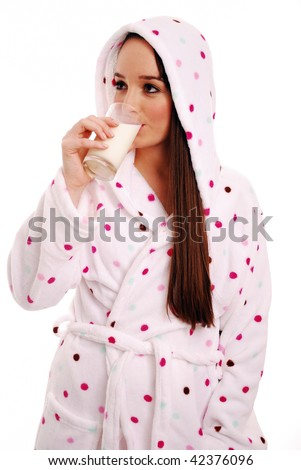 Girl drinking glass of milk before bed on white background - stock photo