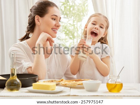 girl drinking milk at the kitchen - stock photo