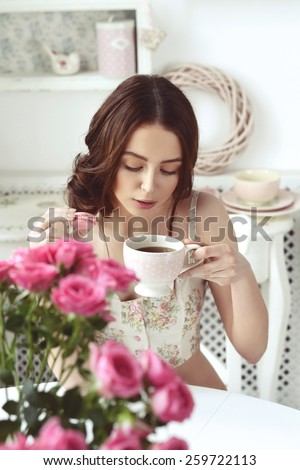 girl drinking tea with a cake in the kitchen at the table with flowers - stock photo