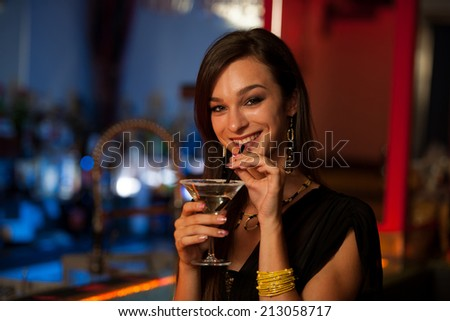 Girl drinks a cocktail in night club - stock photo
