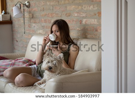 Girl drinks coffee and relax with dog - stock photo