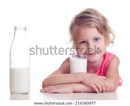 Girl drinks milk from glass on white background - stock photo
