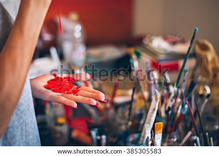 Girl dripping paint on her hand in a messy studio - stock photo