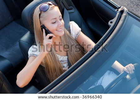 girl driver with mobile phone, in the car - stock photo