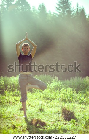 girl during a morning yoga in nature at dawn - stock photo