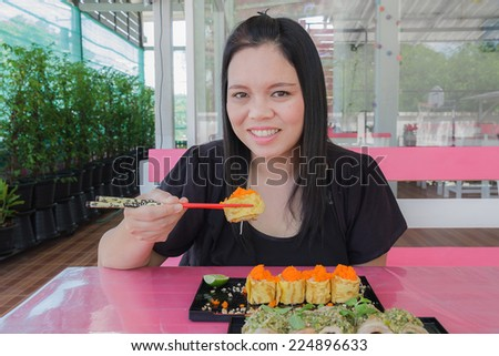 Girl eat sushi egg and bacon chili sauce in restaurant - stock photo