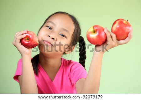 Girl eating a red apple with 3 results to good health - stock photo