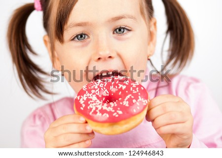 Girl eating an unhealthy doughnut snack. - stock photo