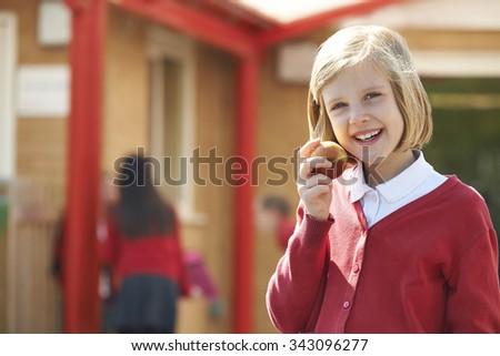 Girl eating apple in playground in school uniform - stock photo
