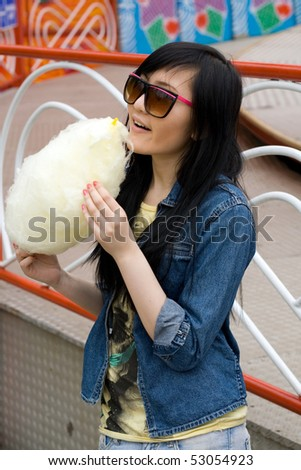Girl eating candy floss - stock photo