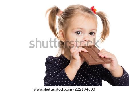 Girl eating chocolate. Two years. - stock photo