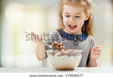 girl eating flakes at the kitchen - stock photo