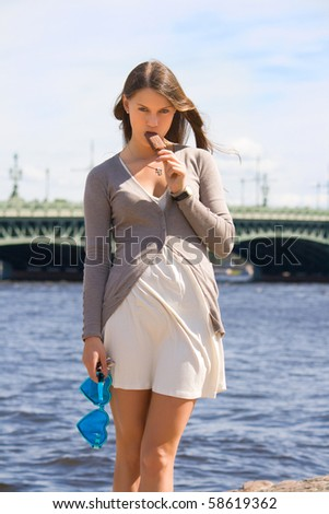 girl eating ice cream on the waterfront - stock photo