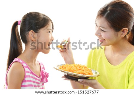 Girl eating meal with mother - stock photo