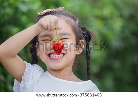 Girl eating strawberries in the berry meadow - stock photo