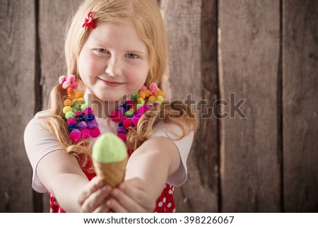 girl eating tasty ice cream over wooden background - stock photo
