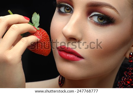 Girl eats strawberry on a black background - stock photo