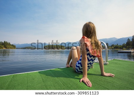 Girl enjoying a Summer Vacation at a beautiful mountain lake. View from behind with a gorgeous rocky mountain scene behind her - stock photo