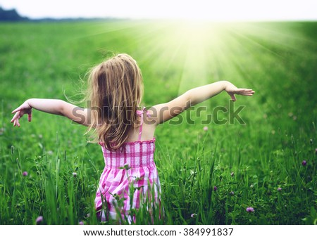 Girl enjoying nature in meadow. Outstretched arms fresh morning air summer field at sunrise - stock photo