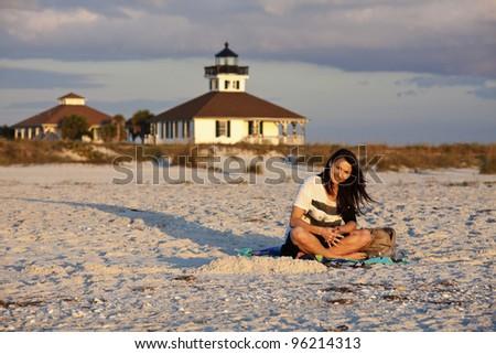 Girl enjoying the beach with Boca Grande Lighthosue - stock photo