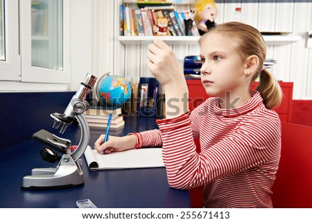 Girl examines drug for the microscope - stock photo