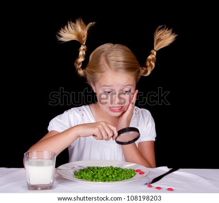 Girl examining bugs on table with magnifying glass, isolated on black - stock photo