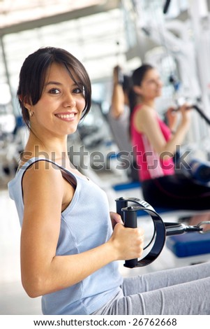 Girl exercising on the machines at the gym - stock photo