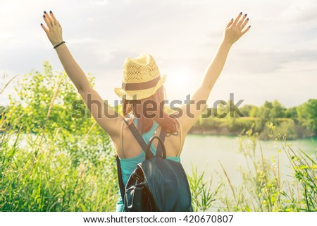 Girl expressing her freedom raising her arms to the sky - Portrait of an attractive caucasian hiker - stock photo