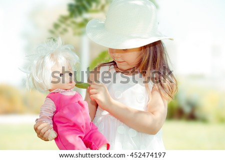 Girl feeding her doll.  Closeup portrait head shot of playing giving to eat to her doll toy looking at you camera isolated outdoor green background Positive human emotions. Mixt race Childhood concept - stock photo