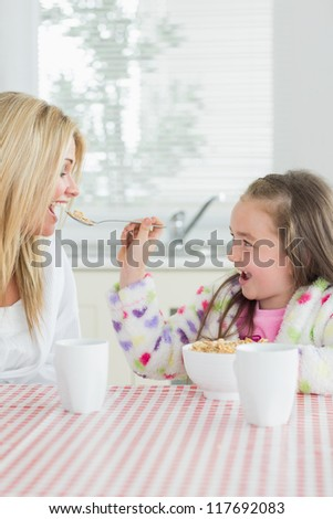 Girl feeding her mum cereal at the kitchen - stock photo