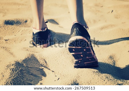 girl feet in sneakers go away on the sand. tinted, horizontal - stock photo