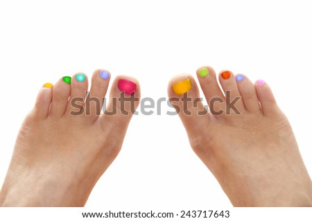Girl feet with rainbow colorful nails isolated on white background - stock photo