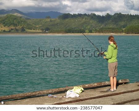 Girl fishing, New Zealand - stock photo