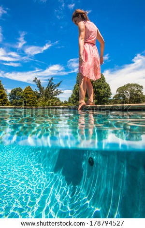 Girl Foot Test Water Pool Summer Teen girl foot tests the swimming pool waters summer season - stock photo