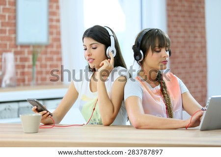 Girl friends connected each one with a different support - stock photo